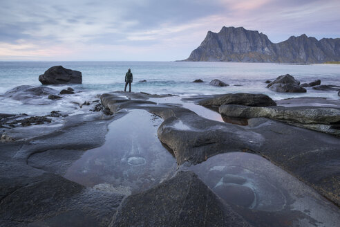 Man standing on rocky beach and looking at sea - AURF04692