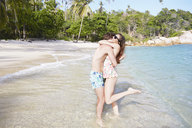 Young couple embracing on beach - LUXF00094