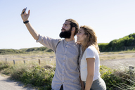 Young couple taking smartphone selfies on the beach - HHLMF00398