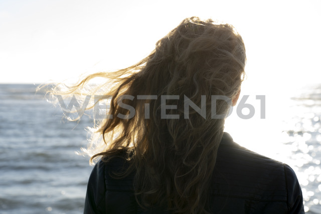 Blond woman looking at the sea, rear view - HHLMF00443