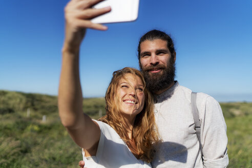 Young couple taking smartphone selfies on the beach - HHLMF00452