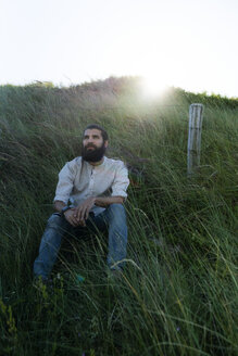 Young man sitting on grass in the dunes, daydreaming - HHLMF00455