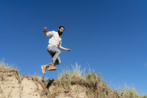 Young man jumping from a sand dune - HHLMF00464