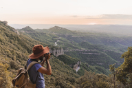 Spain, Barcelona, Montserrat, man with backpack taking photo of view at sunset - AFVF01551