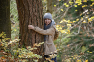 Portrait of smiling teenage girl hugging tree trunk in autumnal forest - LBF02044