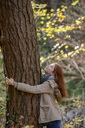 Smiling teenage girl hugging tree trunk in autumnal forest - LBF02047