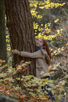 Smiling teenage girl hugging tree trunk in autumnal forest - LBF02050
