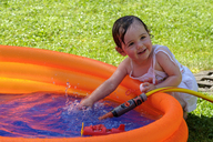 Portrait of smiling baby girl splashing with water in a paddling pool in the garden - LBF02059
