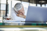 Exhausted businessman sleeping in front of laptop - RBF06602