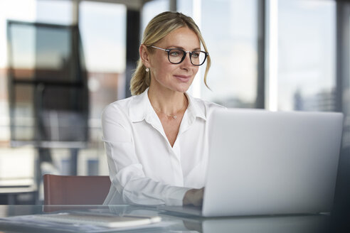 Businesswoman working in office, using laptop - RBF06638