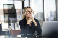Businesswoman sitting at desk, thinking - RBF06641