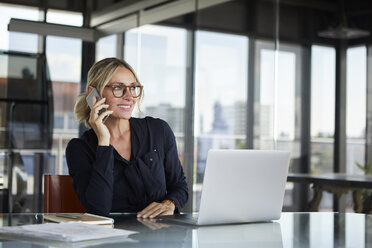 Businesswoman sitting in office, talking on the phone - RBF06644
