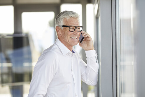 Successful businessman using smartphone, talking on the phone - RBF06650