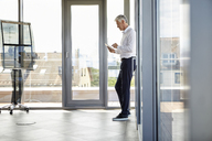 Successful businessman standing in office, using digital tablet - RBF06662