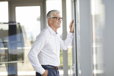 Confident businessman standing in office, looking out of window - RBF06671