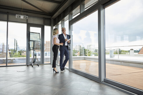 Businessman and woman standing in office, discussing project, holding documents - RBF06677