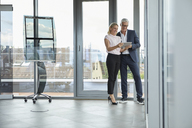 Businessman and woman standing in office, discussing project, looking at digital tabet - RBF06680