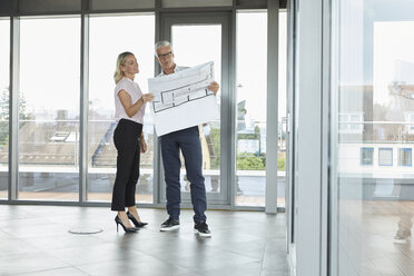 Businessman and woman standing in office, discussing blueprint - RBF06683