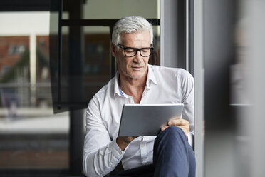 Serene businessman sitting on ground in office, using digital tablet - RBF06689