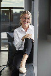 Serene businesswoman sitting on ground, smiling - RBF06692