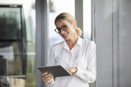 Businesswoman leaning on window, using digital tablet - RBF06695
