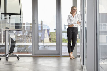 Successful businesswoman standing in office, looking out of window, with arms crossed - RBF06701