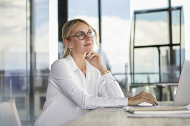Businesswoman sitting at desk, thinking - RBF06704