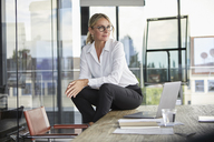 Successful businesswoman sitting on desk, contemplating - RBF06707
