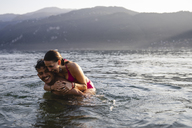 Happy playful young couple in a lake - MRAF00289