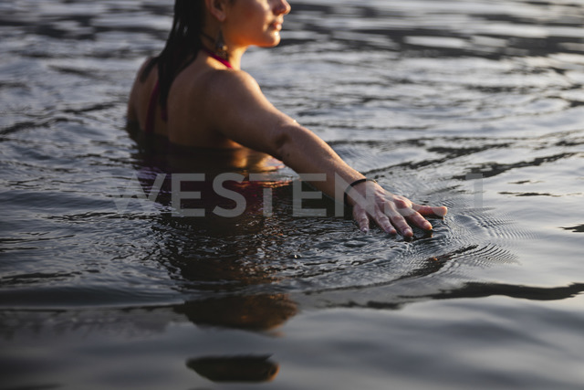 Hand of young woman touching the water surface in a lake - MRAF00304