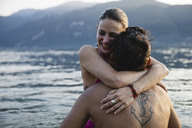 Happy young couple hugging in a lake - MRAF00307
