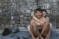 Portrait of affectionate young couple in swimwear sitting at a stone wall - MRAF00310