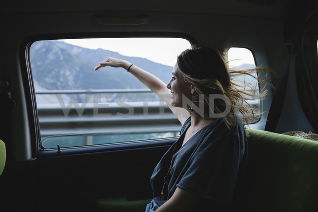 Happy young woman sitting on backseat in a car looking out of window - MRAF00319