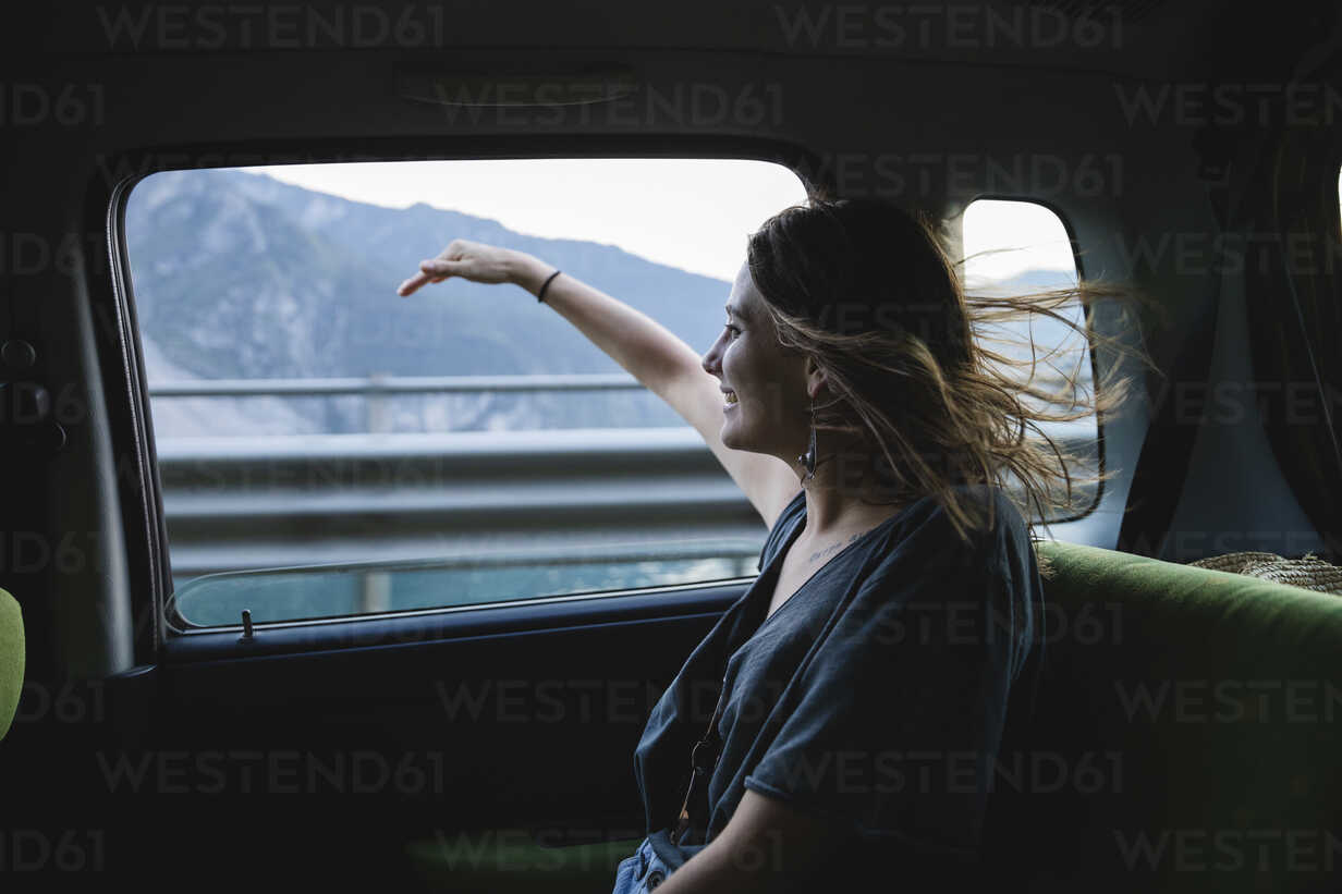 Happy young woman sitting on backseat in a car looking out of window - MRAF00319 - Michela Ravasio/Westend61