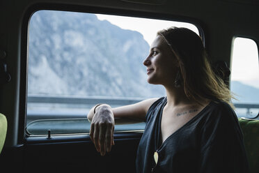 Smiling young woman sitting on backseat in a car looking out of window - MRAF00322