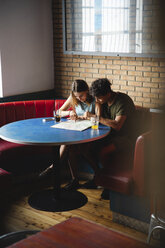 Young couple sitting at table in a cafe with map - MRAF00328