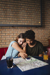 Affectionate young couple sitting at table in a cafe with map and cell phone - MRAF00331