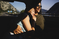 Smiling affectionate young couple sitting on backseat in a car - MRAF00334