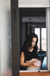Serious beautiful young woman with cup of coffee at the window at home - KKAF01815