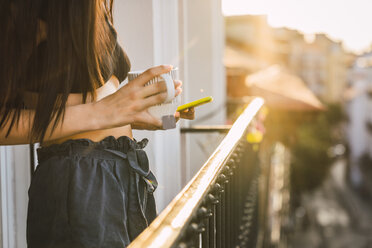 Close-up of young woman on balcony above the city at sunset holding cell phone and cup of tea - KKAF01836