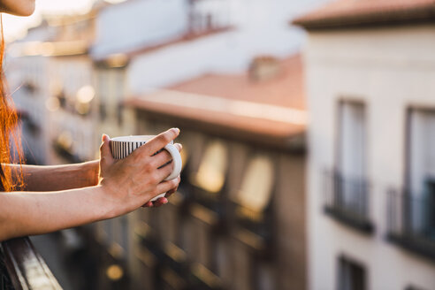 Hands of woman on balcony above the city at sunset holding cup of coffee - KKAF01839
