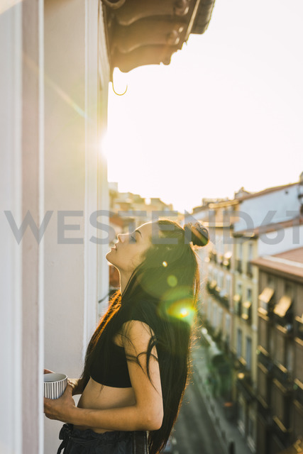Beautiful young woman on balcony above the city at sunset - KKAF01842
