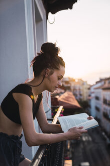 Beautiful young woman on balcony above the city at sunset reading a book - KKAF01848