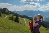 Germany, Bavaria, Brauneck near Lenggries, young woman in alpine landscape drinking water from bottle - LBF02072