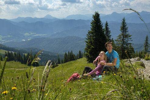 Germany, Bavaria, Brauneck near Lenggries, happy young couple having a break sitting in meadow in alpine landscape - LBF02087