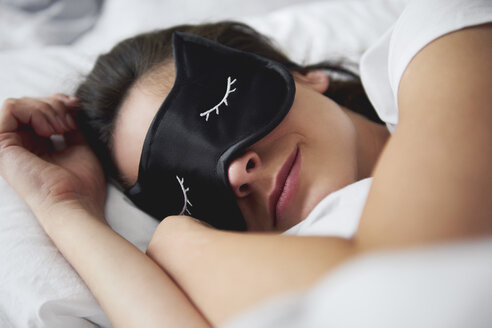 Portrait of young woman with sleep mask in bed - ABIF01007