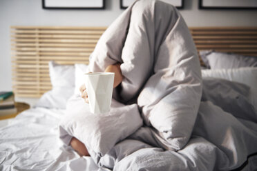 Woman hidden under blanket demanding coffee - ABIF01013