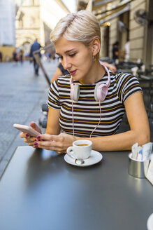 Italy, Florence, portrait of young woman at pavement cafe looking at smartphone - MGIF00244