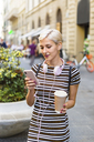 Portrait of young woman wearing striped dress standing on street with coffee to go looking at cell phone - MGIF00247