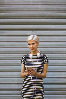 Portrait of young woman with headphones and smartphone wearing striped dress in front of roller shutter - MGIF00250
